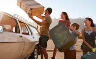 Family packing luggage for a summer road trip