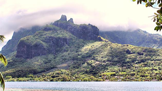 Green and Blue water in bay with green mountains towering above