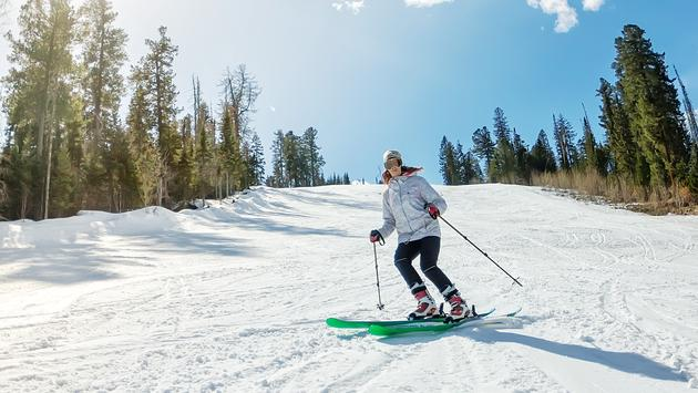 Young girl skiing on a snowy track against the sky