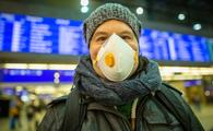 Man wearing a mask at a train station