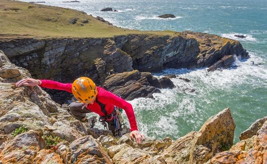 A rock climber reaches the top of a sea cliff at Rhoscolyn, Holy Island.