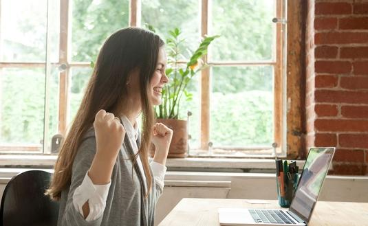 Excited woman on laptop