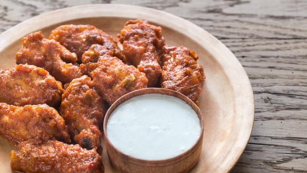 Fried chicken wings with dipping sauce.