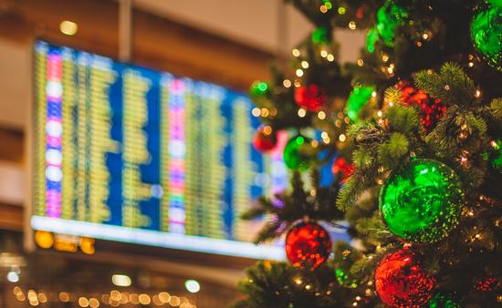 Christmas tree in front of an airport departures board.