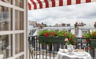 Balcony with red and white stripped awning, white tablecloths and fine china