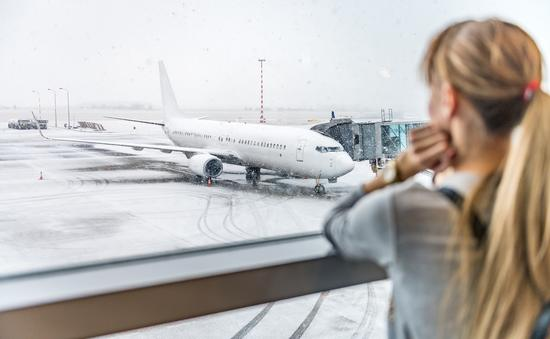 Woman gazing at snowy tarmac and delayed plane flight.