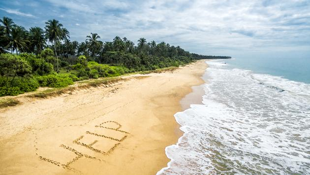 The message 'Help' written on the sands of a tropical beach.