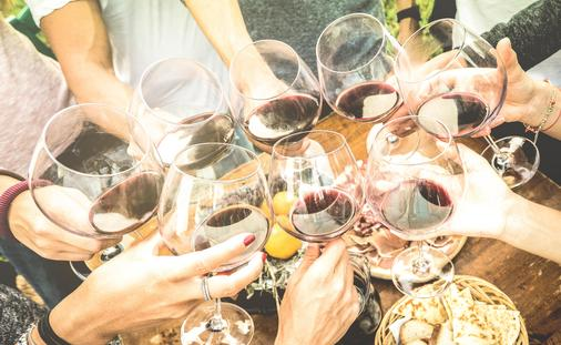 Friends hands toasting red wine glass