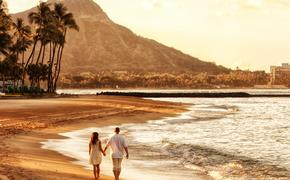 Couple walking on Waikiki Beach, Honolulu, Hawaii.