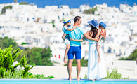 Family of four on european vacation on the edge of pool (PHOTO: Photo via travnikovstudio / iStock / Getty Images Plus)