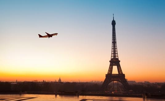 Eiffel tower at sunrise and airplane in the blue sky (Photo via anyaberkut / iStock Editorial / Getty Images Plus)