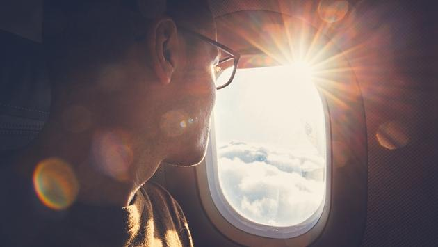 Passenger watches the sunrise through an airplane window