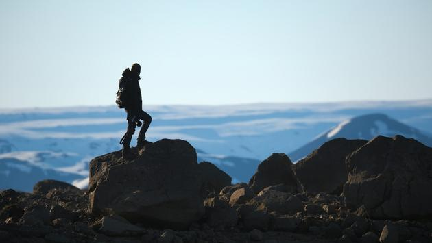 A traveler standing on a cliff in the Icelandic Highlands