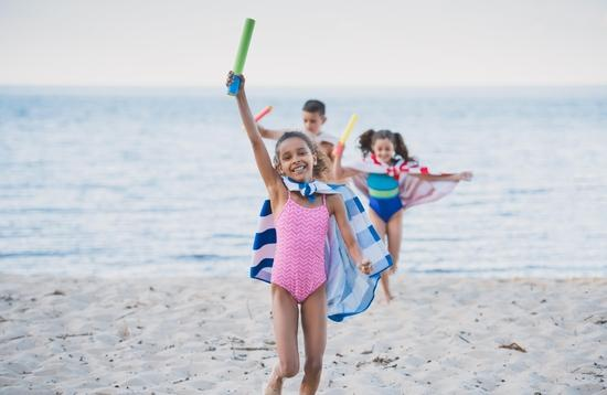 kids in towels with water toys in hands running on beach
