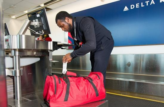 Delta employee tagging a checked bag