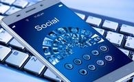 Social media symbols on a smart phone on top of a keyboard