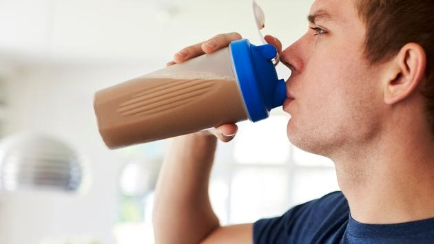 Man drinking protein shake from a shaker bottle