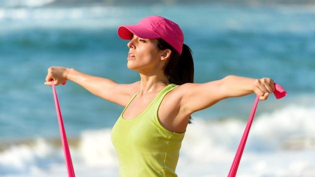 Woman training with a resistance band on the beach