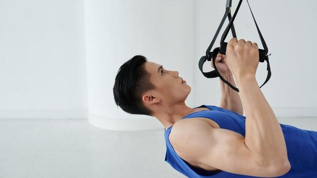 Man working out with strength training straps