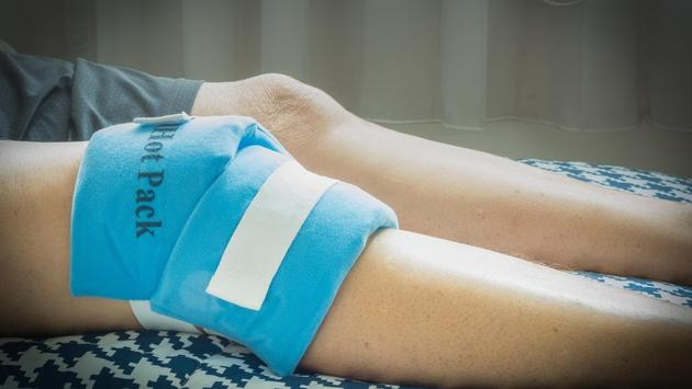 Man using hot and cold gel pack for knee pain relief