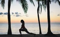 A woman stretching on the beach in Riviera Maya, Mexico
