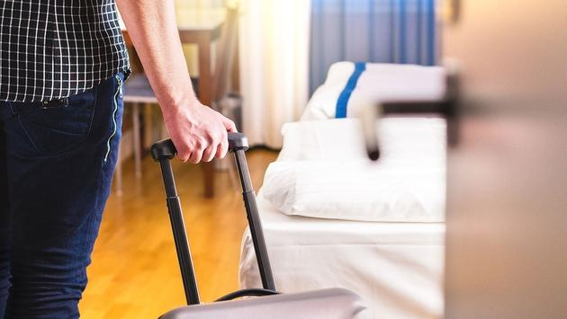 Man pulling suitcase and entering hotel room (Photo via Tero Vesalainen / iStock / Getty Images Plus)