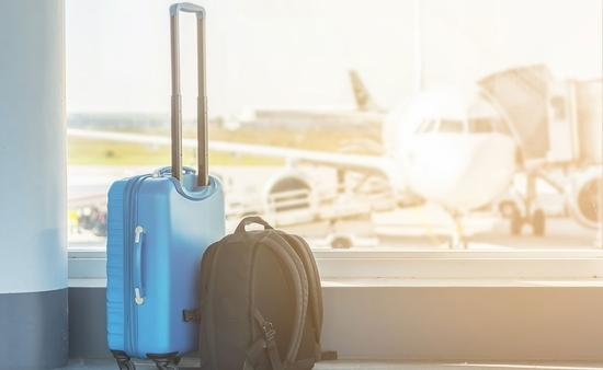 Hand luggage at the airport in front of an airplane (Photo via Ralf Geithe / iStock / Getty Images Plus)