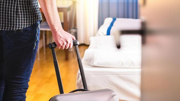 pulling suitcase and entering hotel room