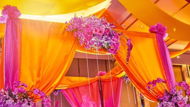 Colorful stage decoration for bride and groom in sangeet night of Indian wedding