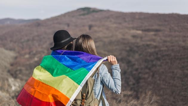 A lesbian couple stands holding the rainbow flag