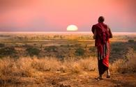 Masai man, wearing traditional blankets, overlooks Serengeti in Tanzania as the colorful sunset fills the sky. Wild grass in the forground. (photo courtesy of jocrebbin /iStock / Getty Images Plus)