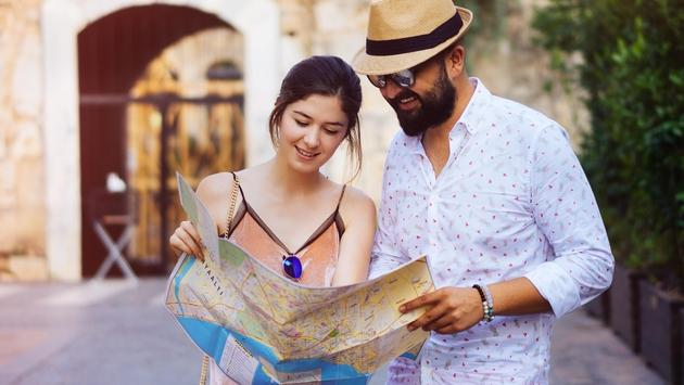 Happy tourists couple holding map