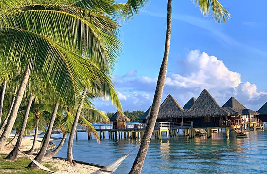 Palm trees and hammock on beach with overwater bungalows on lagoon