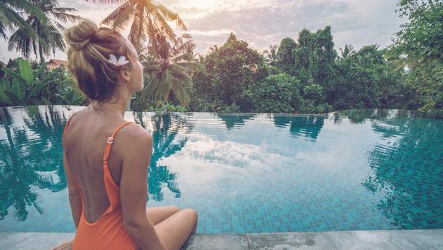 Woman by the edge of an infinity pool enjoying tropical climate in Ubud, Bali.