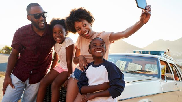 Family posing for selfie ahead of a road trip