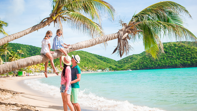Happy family relaxing on tropical beach (PHOTO: Photo via travnikovstudio / iStock / Getty Images Plus)