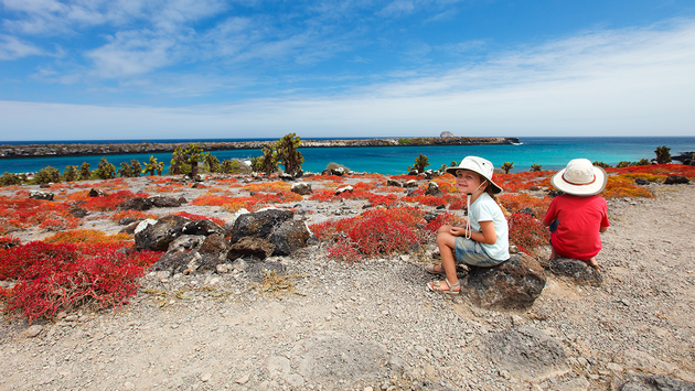 Two kids at scenic terrain on Galapagos South Plaza island (PHOTO: Photo via shalamov / iStock / Getty Images Plus)