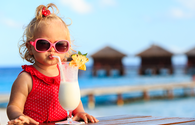 cute little girl drinking smoothie on tropical beach (PHOTO: Photo via Nadezhda1906 / iStock / Getty Images Plus)