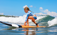 Young surfer rides on surfboard with fun on sea waves (PHOTO: Photo via Bicho_raro / iStock / Getty Images Plus)