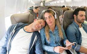 Man sleeping on a woman's shoulder aboard a plane in economy seating.