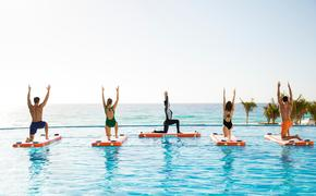 Couples participating in a yoga class at Le Blanc Spa Resort's Sol Pool.