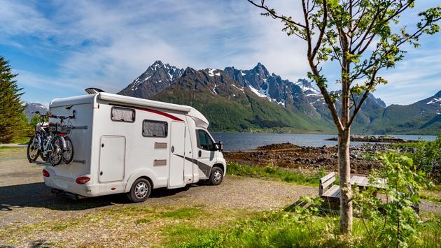 An RV parked beside a mountain lake.