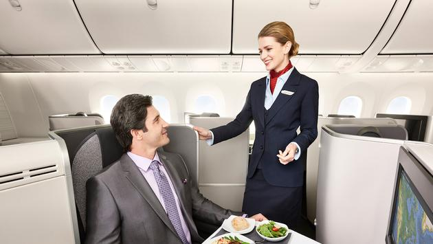 Flight attendant assisting passenger in Air Canada's new International Business Class cabin on the Boeing 787 Dreamliner
