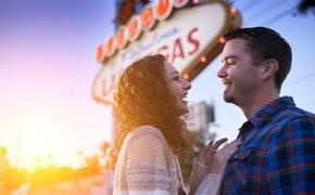 romantic couple in front of welcome to las vegas sign