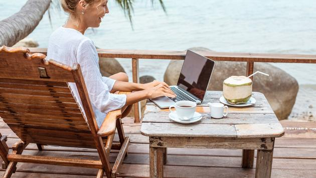 Woman working on a laptop in a tropical destination.