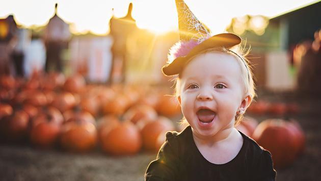 Girl at pumpkin patch on Halloween