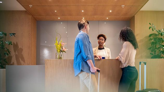 Couple talking to receptionist at hotel lobby