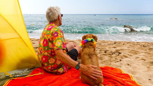 Elderly man with dog on beach