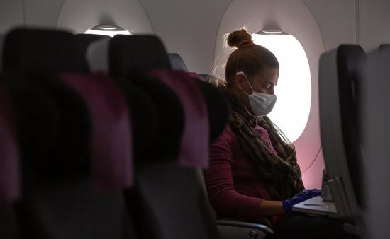 A woman wearing a face mask on an airplane