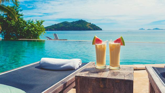 PHOTO: Cocktails by the pool with beach in the background. (Photo via courtneyk / iStock / Getty Images Plus)